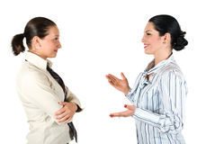 Business woman conversation. Two cheerful businesswoman have a conversation,the brunette woman explaining something and gesturing with hands while the other Stock Images