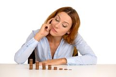 Business woman corporate executive sitting at table with growing stack of coins Royalty Free Stock Photography