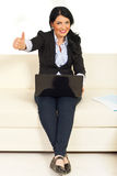 Business woman on couch gives thumbs Royalty Free Stock Images
