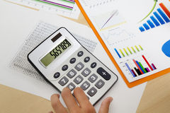 Business woman counting on calculator sitting at the table. Photo of hands under document and pressing calculator buttons Royalty Free Stock Photos