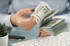 Business woman, counting cash us dollars above white computer keyboard royalty free stock photography