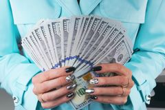 Business woman counting money in hands. Handful of money. Offering money. Women`s hands hold money denominations of 100 dollars. Royalty Free Stock Photo