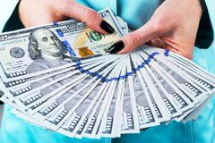 Business woman counting money in hands. Handful of money. Offering money. Women`s hands hold money denominations of 100 dollars. Stock Image