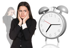 Business woman cover her ears. Alarm clock Stock Image