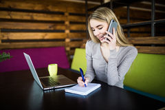 Business woman at coworking  speak at phone and make notice Stock Photos