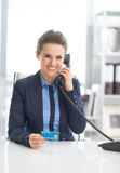 Business woman with credit card talking phone Royalty Free Stock Images