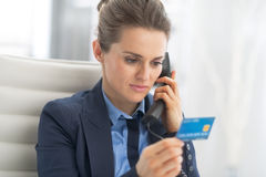 Business woman with credit card talking phone. In office Stock Photo