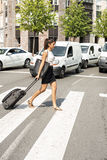 Business woman crossing the street with luggage. Royalty Free Stock Photos