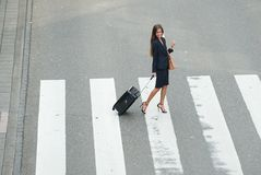 Business woman crossing street with travel bags. Portrait of a business woman crossing the street with travel bags Royalty Free Stock Image