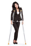 Business woman with crutches Stock Photos