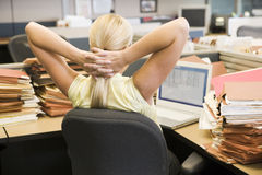 Business woman in cubicle relaxing Royalty Free Stock Photography