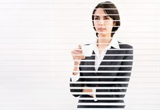 Business woman. With cup of coffe looking through a venetian blind in an office Royalty Free Stock Photos