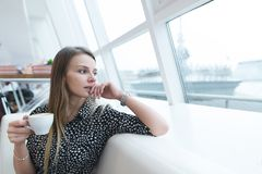 A business woman with a cup of coffee in her hands sits in a modern, light restaurant and looks out the window. A serious woman looks in the window and thinks Royalty Free Stock Images