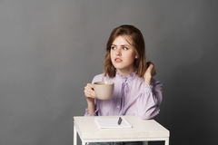 Business woman with cup. Studio photography. One on a gray background. Royalty Free Stock Photos