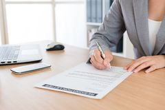 Business woman decided retired from company. Closeup of business women decided retired from company and writing personal resignation letter explaining plan in Stock Image