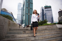 Business woman descends the stairs to the street stock photography