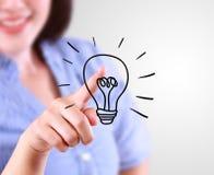 Business woman designate a lamp of idea Royalty Free Stock Photos