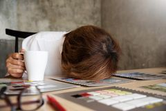 Business woman Designer Sleeping while working. Exhausted, Tired from overwork or overtime. Early morning stock photography