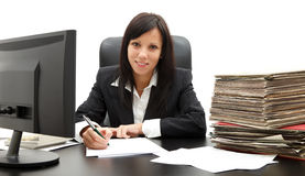 Business woman at desk. Attractive young business woman in black suit at her desk Stock Images