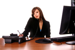 Business Woman At Desk 3. Redheaded business woman in black business suit at her desk and talking on a corded phone isolated over white