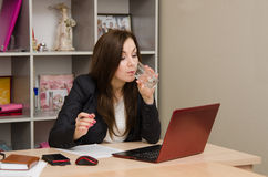 Business woman at the desk drinking water Royalty Free Stock Images