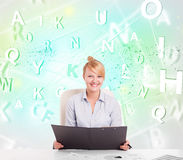 Business woman at desk with green word cloud Stock Photography