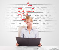 Business woman at desk with labyrinth and arrow Stock Photography