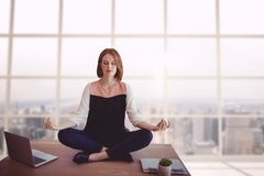 Business woman on a desk meditating Stock Photography