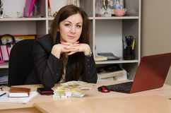 Business woman at desk with a stack of money Stock Image
