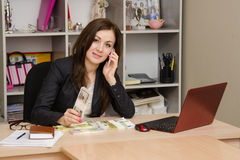Business woman at a desk with stack of money talking on phone Stock Photo