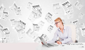 Business woman at desk with stock market newspapers Royalty Free Stock Photos