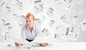 Business woman at desk with stock market newspapers Royalty Free Stock Photography