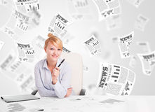 Business woman at desk with stock market newspapers Royalty Free Stock Image