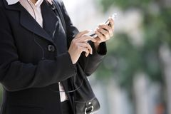 Business Woman Dialing On Cell Phone. Mid section of business woman dialing on cell phone Stock Photo