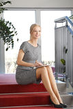 Business woman with digital tablet. Full length portrait of mature business woman sitting at staircase while tounching digital tablet royalty free stock photos