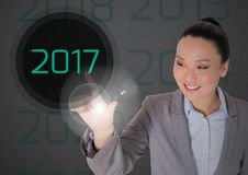 Business woman in digitally generated background touching 2017. Smiling business woman in digitally generated background touching 2017 new year Royalty Free Stock Image