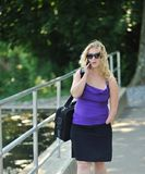 Business woman with disability on phone. Portrait of attractive blonde business woman who is missing part of left arm (congenital amputation) walking and talking Royalty Free Stock Photos