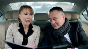 Business woman disagree with terms of contract. Two business partners in the backseat of a car stock video