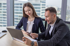 Business woman discusses the report with his colleague at work. Young asian business women in suit discusses the report with his colleague male at work in office Royalty Free Stock Photography
