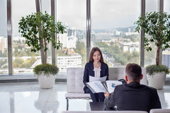 Business woman discusses the report with his colleague at work royalty free stock photo