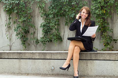 Business woman with document talks on smart mobile cell phone ou Royalty Free Stock Photos