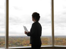 Business woman with documents. Standing near the window and having a short rest Stock Images