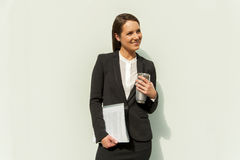 Business woman with documents and coffee standing by white wall Stock Images