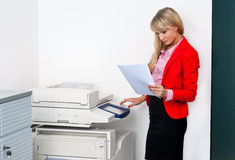 Business woman with documents standing next to printer. Attractive blonde business woman with documents standing next to printer royalty free stock photos