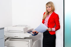 Business woman with documents standing next to printer. Attractive blonde business woman with documents standing next to office printer Royalty Free Stock Images