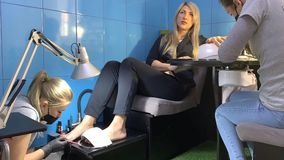 Manicure and Pedicure. Business woman does the combo procedure in the salon: Manicure and Pedicure stock video footage
