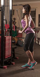 Business woman doing exercise on a fitness machine in a fitness center Royalty Free Stock Image