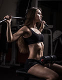 Business woman doing exercise on a fitness machine in a fitness club. Stock Photography