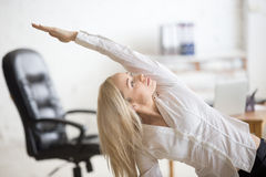 Business woman doing fitness exercise. Business and healthy lifestyle concept. Portrait of young office woman doing fitness exercise at workplace. Happy Royalty Free Stock Photos