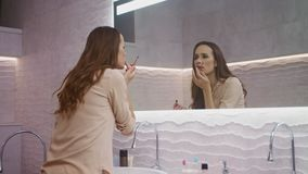 Business woman doing makeup in bathroom. Beauty female person looking at mirror. stock footage